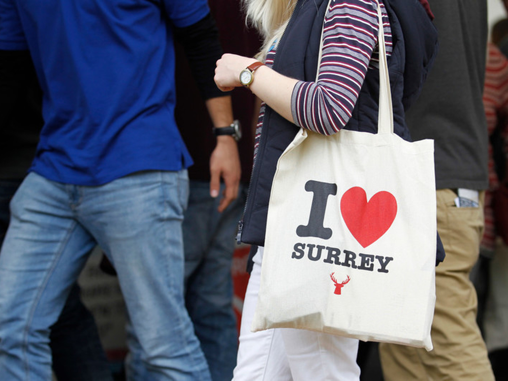 Two people walking, one with an I love Surrey bag