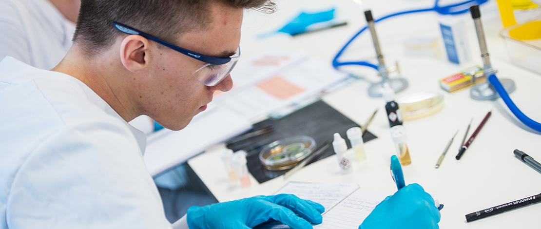 A biosciences student writing notes during experiment